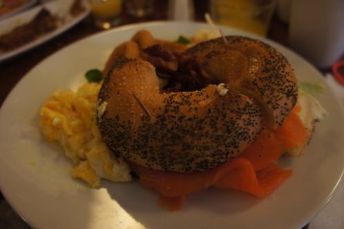 Bagel au saumon avec oeufs brouillés, onion rings et mesclun de salade
